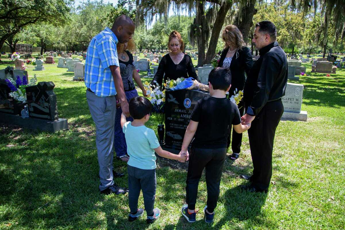 The Amron and Coats family gather in prayer around their the grave of Jamail Amron on Thursday, June 11, 2020, in Aldine. Jamail Amron died suddenly following his arrest by Harris County officers in 2010. Jamail Amron, was allegedly beaten by Harris County officers, according to the civil lawsuit originally filed in 2012 against Harris County and Precinct 4 deputy constable Kevin B. Vailes by Amrom's parents.