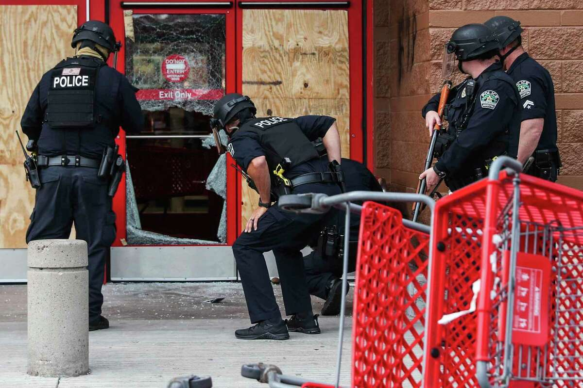 Austin Police Department check the broken door of Target at Capital Plaza after some protesters forcibly entered the store during a rally decrying the death of George Floyd and police brutality in Austin on Sunday, May 31, 2020. George Floyd died while in police custody in Minneapolis on Memorial Day. (Lola Gomez/Austin American-Statesman via AP)