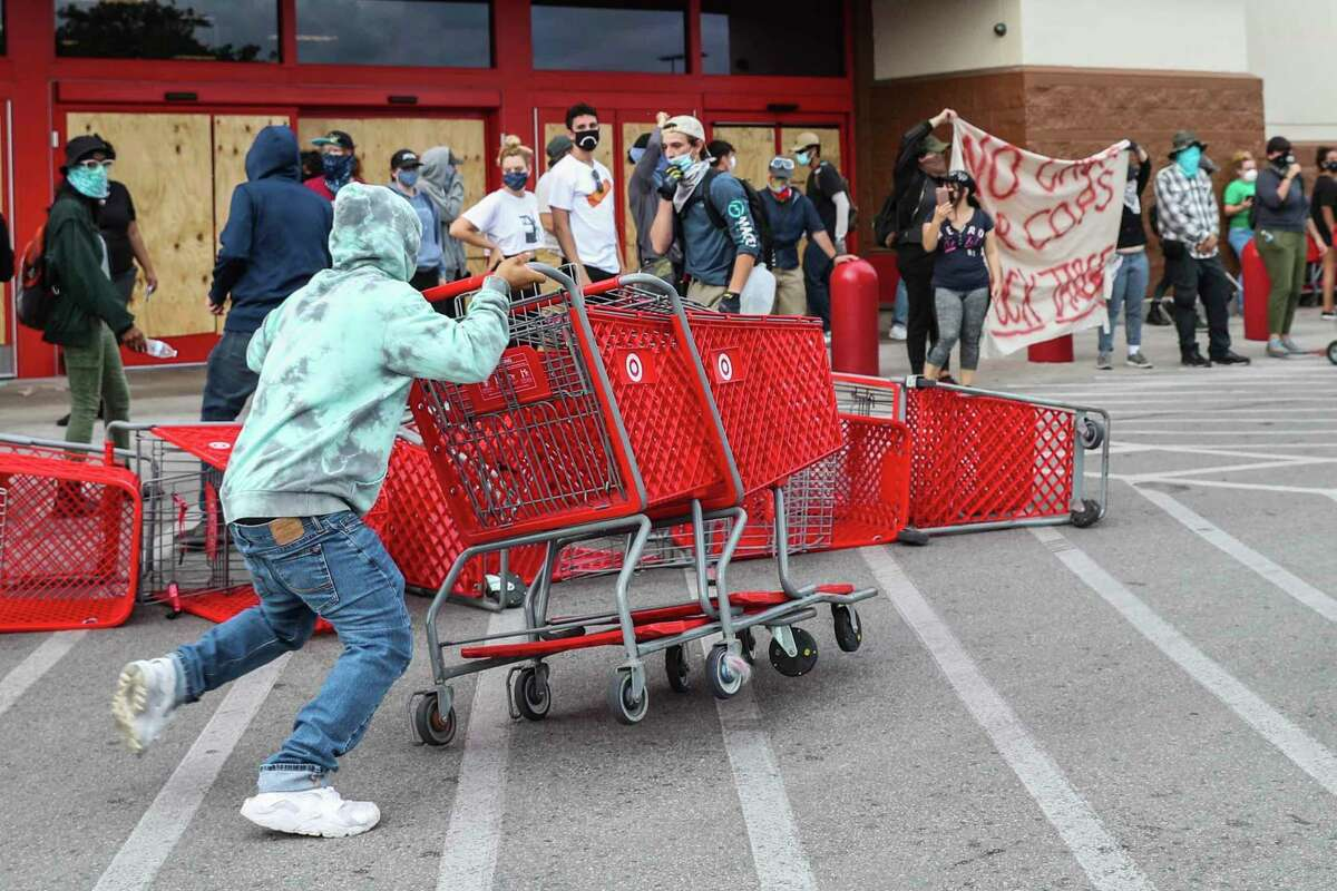 A man places shopping carts in front of the Target entrance during a protest calling for justice over the death of George Floyd in Austin on Sunday, May 31, 2020. George Floyd died while in police custody in Minneapolis on Memorial Day. (Lola Gomez/Austin American-Statesman via AP)