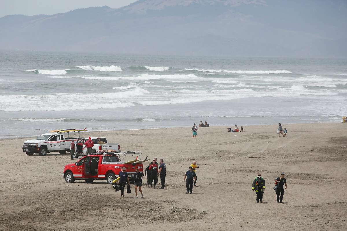 Emergency responders and rescue vehicles are seen on Ocean Beach after 5 victims were rescued on Thursday, June 11, 2020 in San Francisco, Calif.