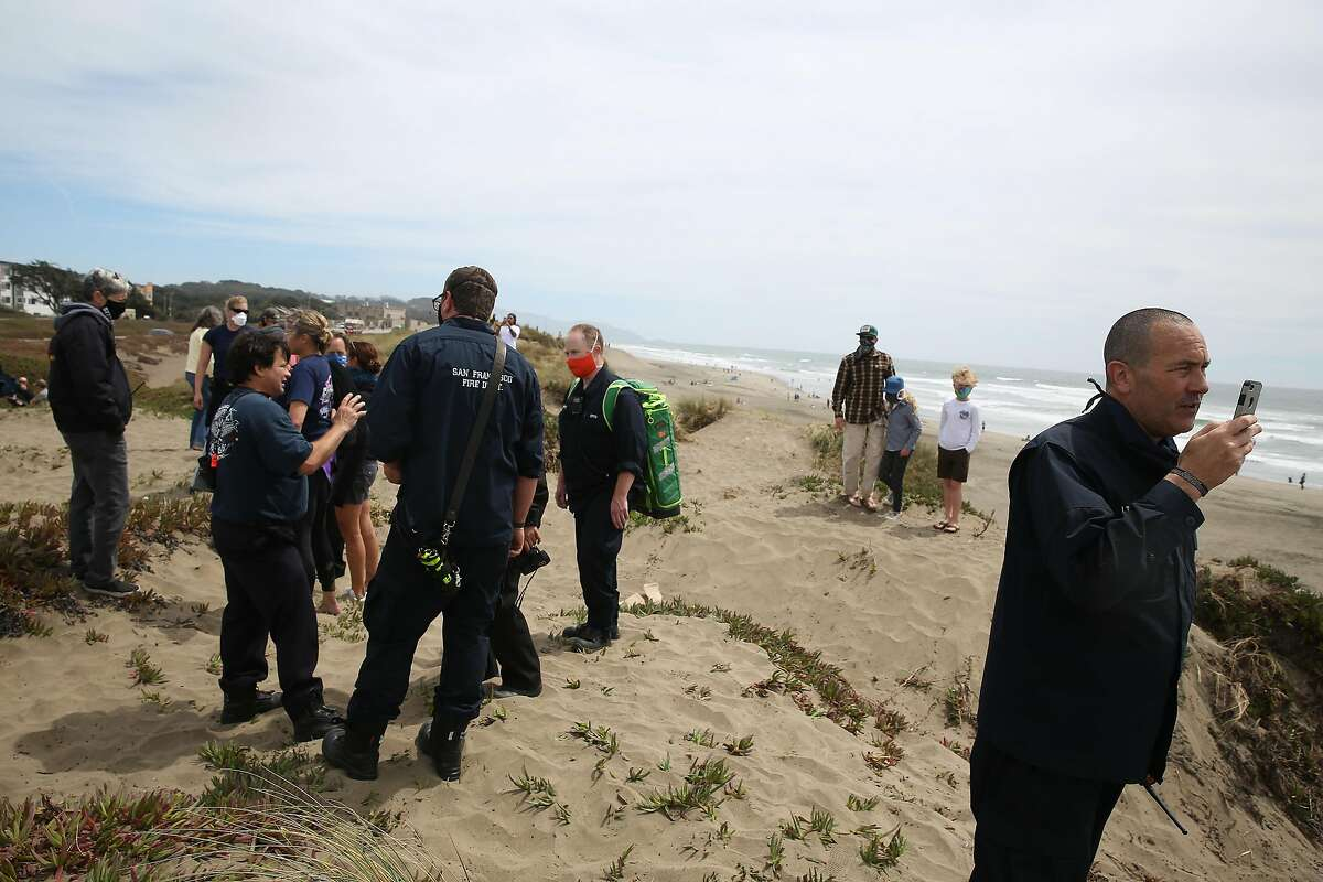 Emergency responders work on a bluff above Ocean Beach after 5 victims were rescued from the water on Thursday, June 11, 2020 in San Francisco, Calif.