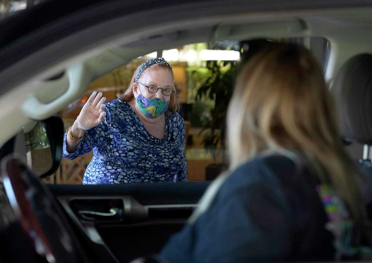 Ruth Steinfeld waves to her granddaughter, Jennifer Beleiff, and great-granddaughters, Madison, 5, and Avery, 2, as they sit in their vehicle during a quick drive by visit outside her residence amid the Covid-19 pandemic Wednesday, April 29, 2020, in Houston. The 87-year-old widower, great-grandmother of seven and grandmother of five, has lived in Houston since 1948 when she came to the United States after the Holocaust. She said she knows the toll of isolation on humans. But she has hope that this won't last long, there's a light at the end of the tunnel.