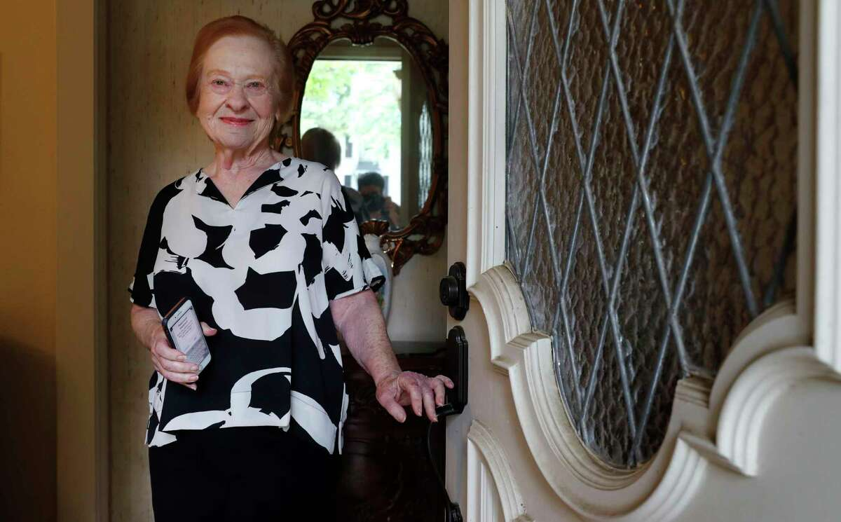 """Dell Kaplan, 81, smiles for a photo in the doorway of her home in Plano, Texas, Friday, May 15, 2020. For Kaplan, the offer to get calls from a stranger just to chat while staying home during the coronavirus pandemic was immediately appealing. """"It gets pretty lonely here by yourself,"""" said Kaplan, a suburban Dallas resident who has been missing meals out with friends, family get-togethers and going to classes at a nearby college. The program being offered by the city of Plano is among those that have popped up across the U.S. during the pandemic to help older adults with a simple offer to engage in small talk."""