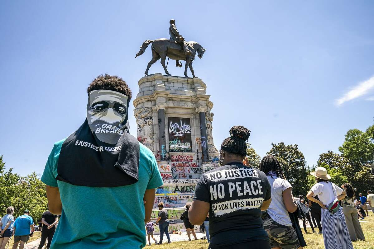 People gather at the Robert E. Lee Monument, now covered by protest graffiti, in Richmond, Va., Sunday, June 7, 2020, following a week of unrest in the U.S. against police brutality and racism in policing. The statue of the Confederate Civil War general is slated for removal at the order of Gov. Ralph Northam. (AP Photo/J. Scott Applewhite)