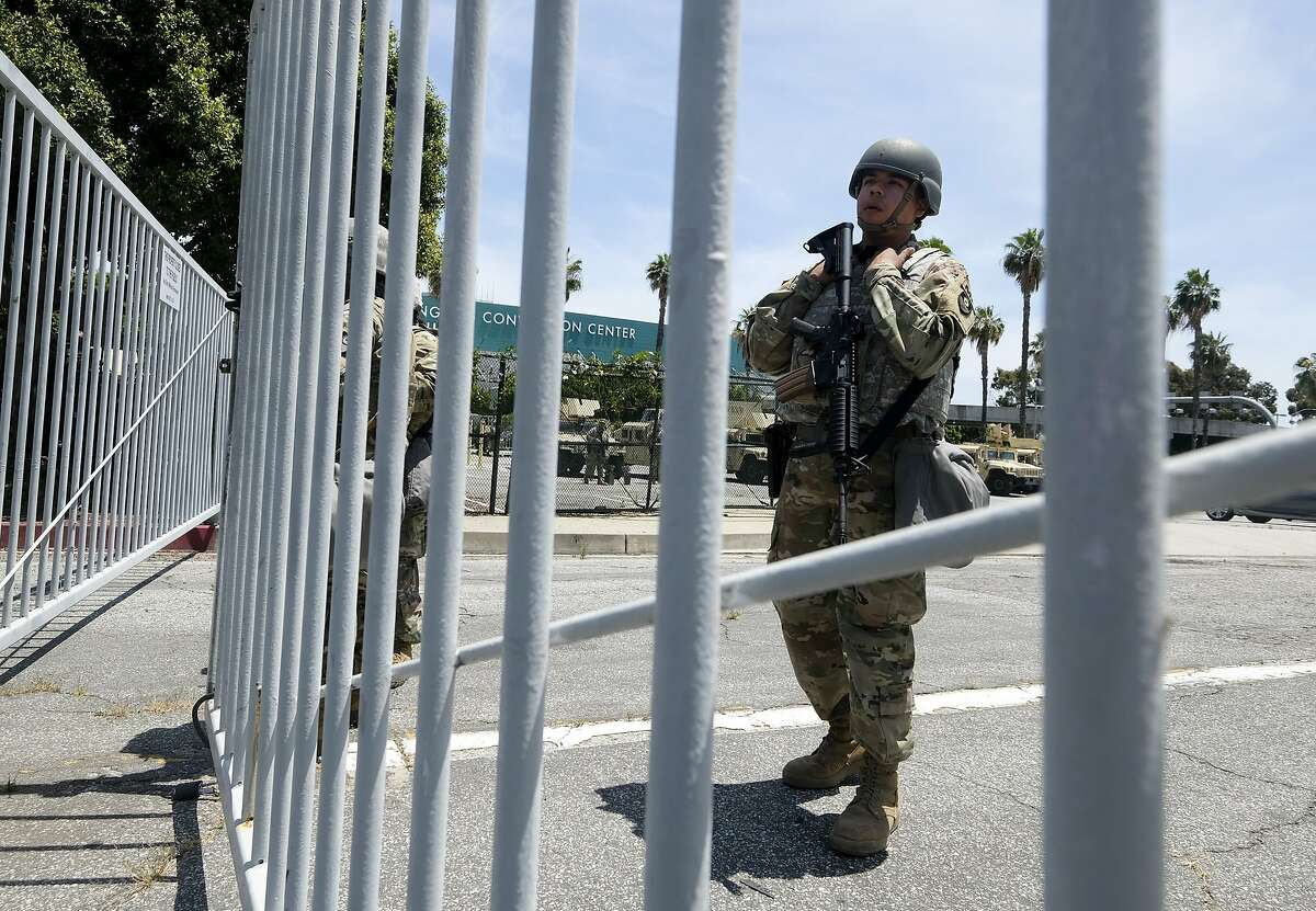 A member of California National Guard stands guard at a parking lot near Los Angeles Convention Center, Sunday, May 31, 2020, in Los Angeles. The National Guard is patrolling Los Angeles as the city begins cleaning up after a night of violence by demonstrators that saw clash with officers and torch police vehicles and pillage stores. (AP Photo/Ringo H.W. Chiu)