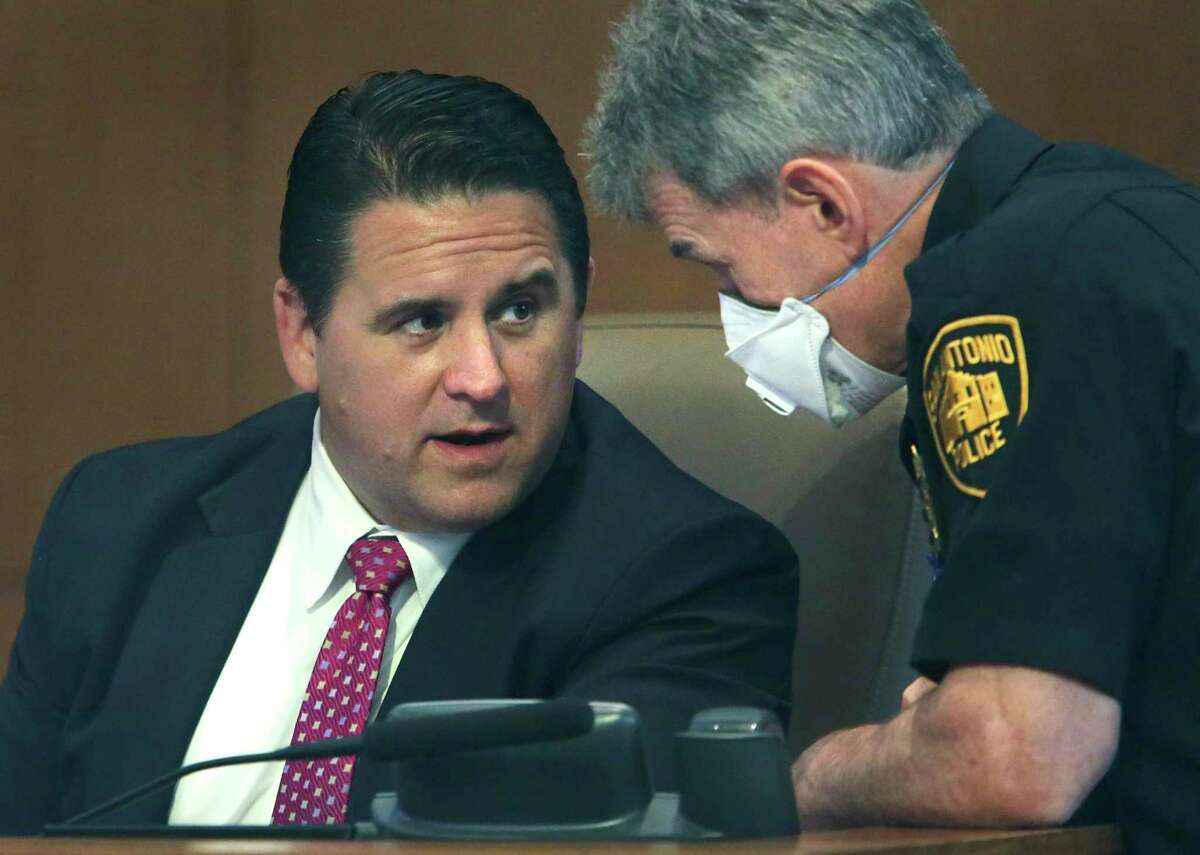 City Manager Erik Walsh talks with Police Chief William McManaus during the council meeting.