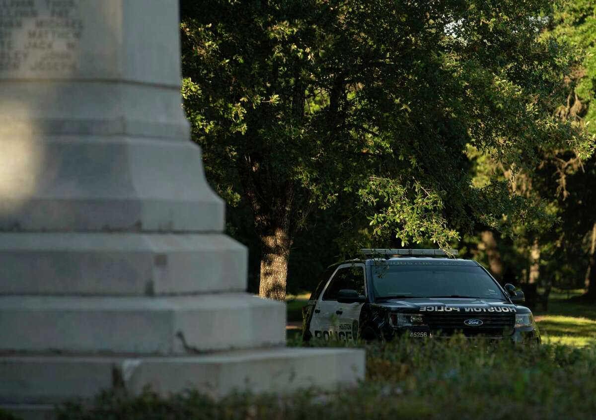 A Houston Police Department patrol car is parked next to the Dick Dowling statue at Hermann Park Thursday, June 11, 2020, in Houston. A Christopher Columbus statue at Bell Park was vandalized.