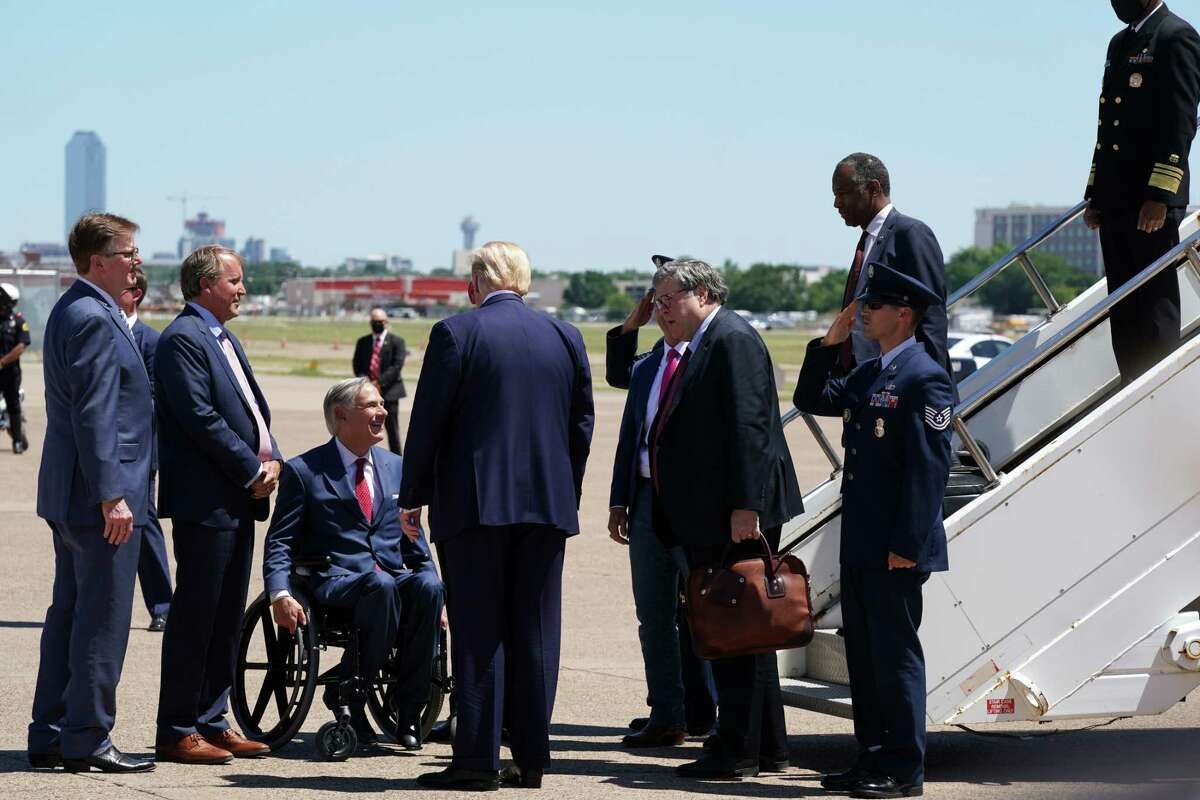 President Donald Trump, back to camera, is greeted upon arrival in Dallas, by Gov. Greg Abbott of Texas, seated, on June 11, 2020. (Anna Moneymaker/The New York Times)