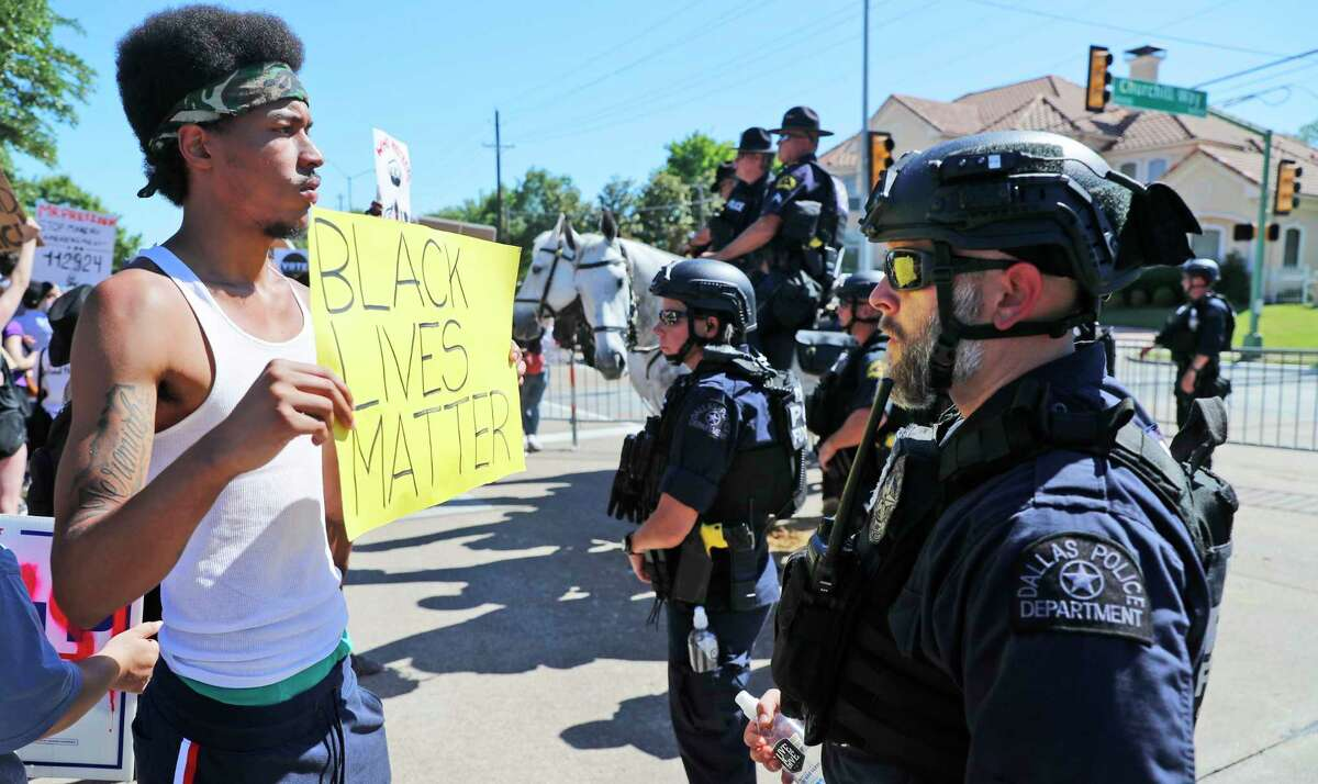A protester and police face each other during a demonstration outside a private meeting with President Donald Trump during a fund raising trip to Dallas, Thursday, June 11, 2020. (AP Photo/LM Otero)