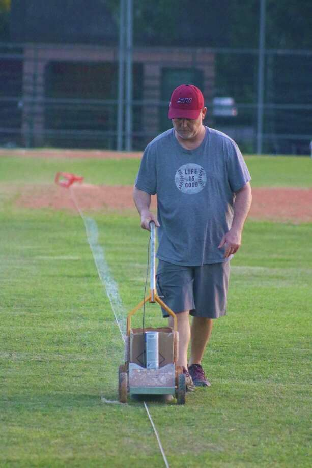 Coach Mark Ulmer applies the right field foul line Wednesday night in preparation for Saturday's five contests that will end NASA Pony's three months of hibernation. Photo: Robert Avery