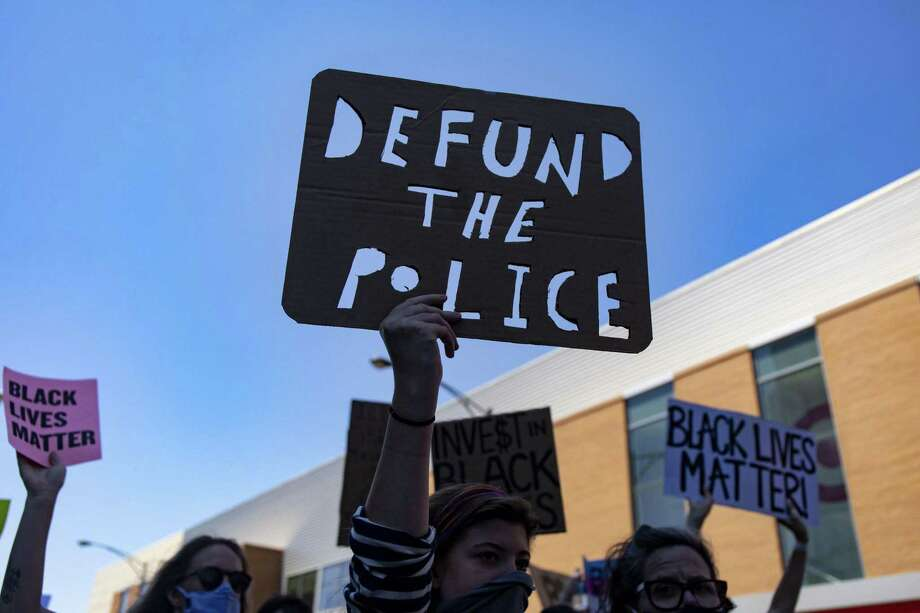 "Protesters carry a ""Defund the Police"" sign during a March of Justice June 6, 2020 in Chicago to demand police accountability. Photo: Brian Cassella / TNS / Chicago Tribune"