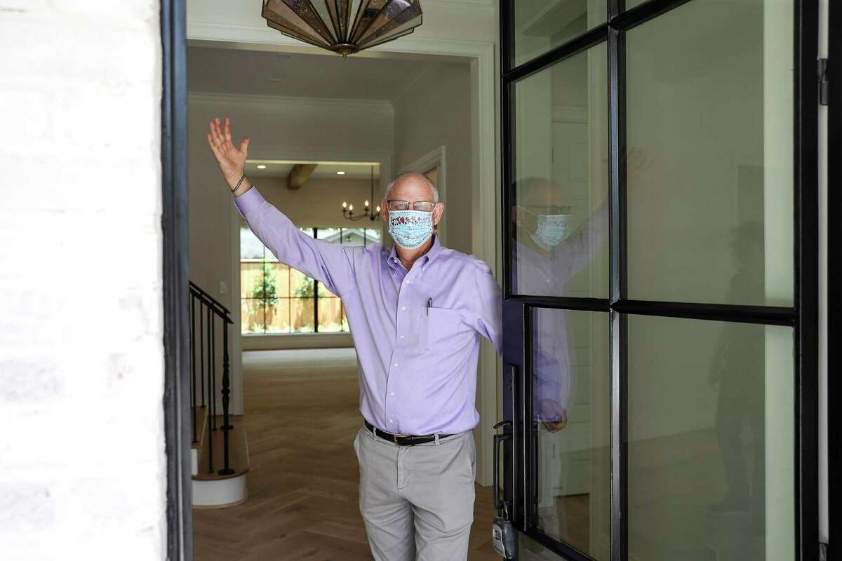 Charlie Neath, a realtor, jokingly poses for a photo as he opens the door during an open house Thursday, June 4, 2020, in the Briargrove neighborhood in Houston.