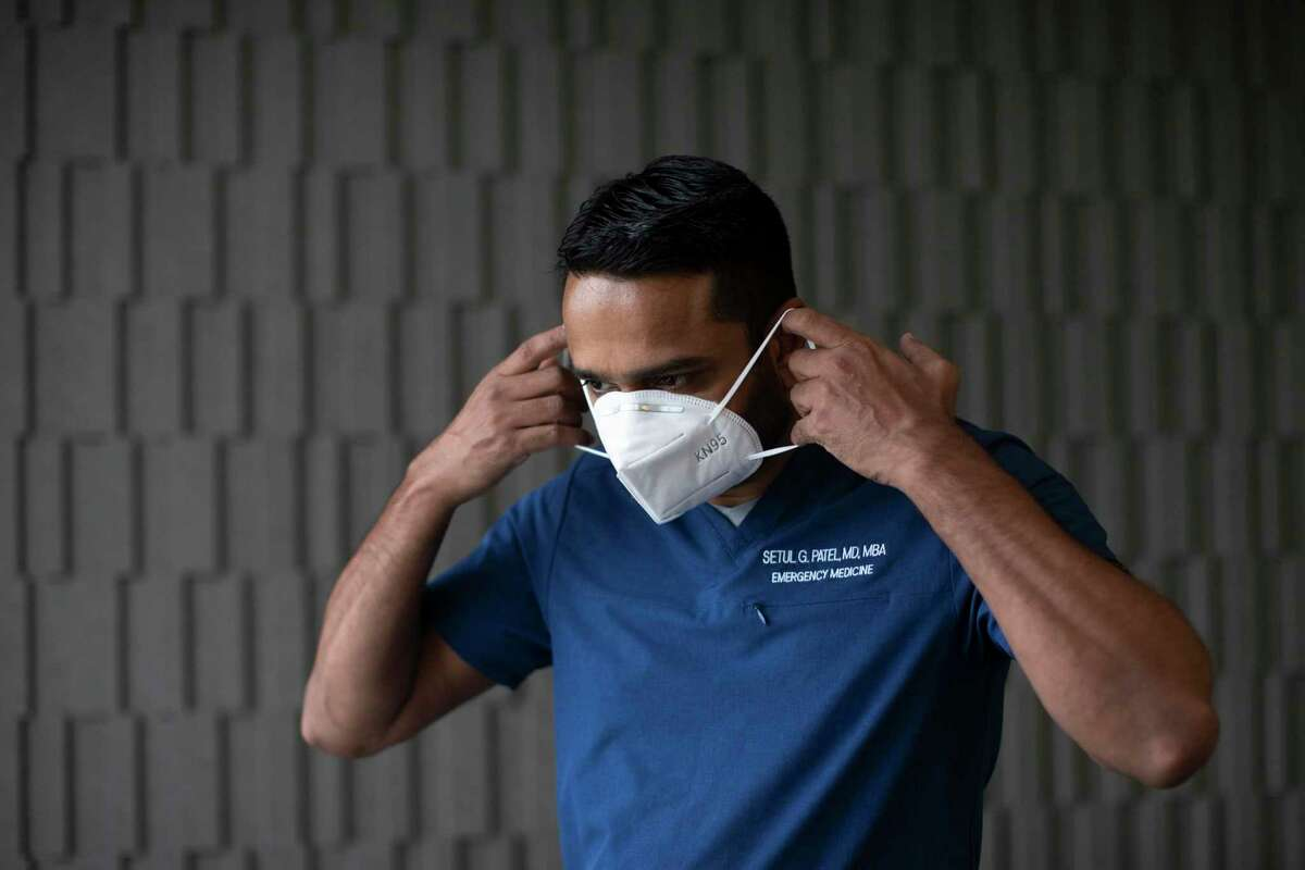 Setul Patel of FormulaMed at Masterson Advisors LLC offices on Thursday, June 4, 2020, in Houston puts on a protective mask. Patel who is an emergency medicine doctor consults with businesses about safe ways to reopen during the pandemic.