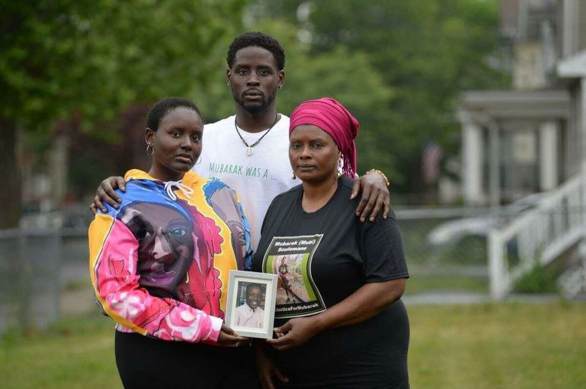 From left, Mariyann Soulemane, her brother Saeed Soulemane and their mother, Omo K. Mohammed pose with a photograph of their brother and son, Mubarak Soulemane, who was shot and killed by a state trooper in West Haven in January after a suspected carjacking.