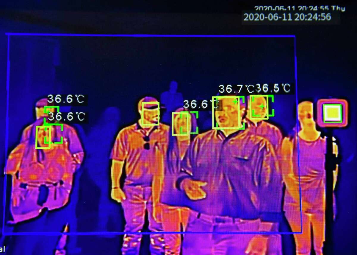Apache staff demonstrate how to use its new Mass Temperature Scan UV-C to screen body temperature Thursday, June 11, 2020, in Houston. The green squares means the body temperatures are normal. This device can scan 5,000 people in 30 minutes, the company said.