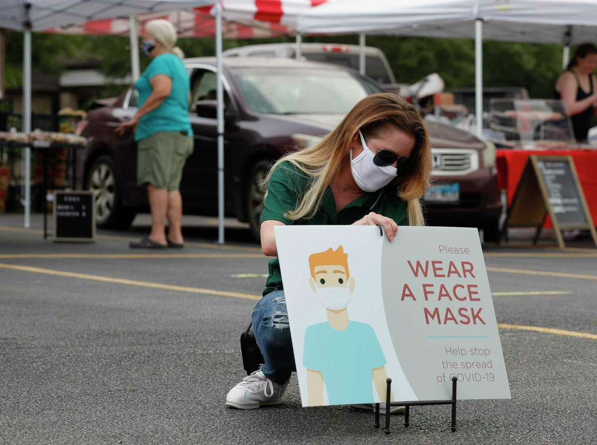 Kelly Lewis secures a sign that ask customers to wear a face mask while shopping at The Woodlands Farmers Market, Saturday, May 23, 2020, in The Woodlands.
