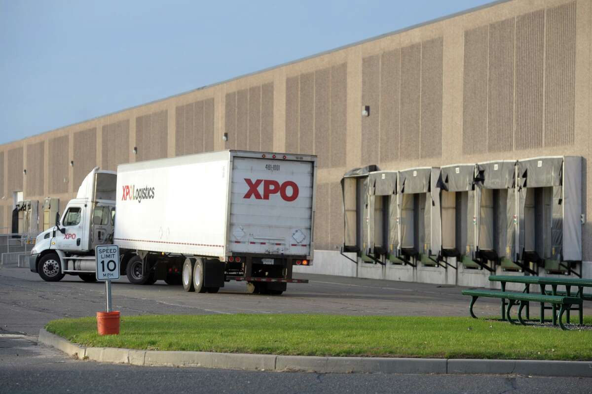 An XPO Logistics truck in November 2019 outside the Long Beach Boulevard warehouses in Stratford, Conn., leased by Amazon for a new distribution center. With the ongoing growth in online commerce, Greenwich-based XPO has grown into one of the world's largest shipping companies with some 100,000 workers, even as it embraces emerging robotic technologies.