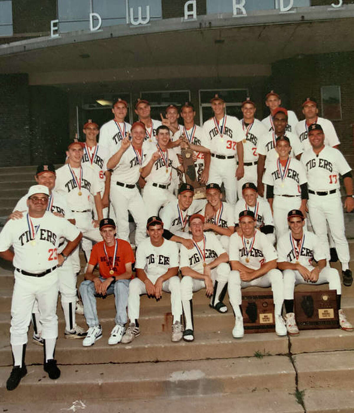 The 1990 Edwardsville baseball team poses with the Class AA state championship trophy on the steps of the high school.