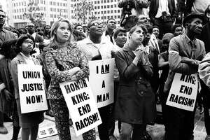 A group of demonstrators holding signs reading 'Union Justice Now', 'Honor King: End Racism!' and 'I Am A Man' march in protest soon after the assassination of Dr. Martin Luther King, Jr., Memphis, TN, April 1968. (Photo by Robert Abbott Sengstacke/Getty Images)