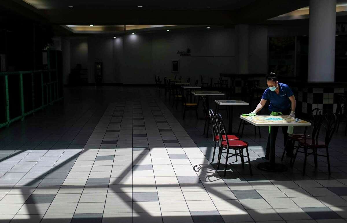 Sara Ponce cleans tables Friday, May 1, 2020, at PlazAmericas mall in Houston. Retailers were allowed to reopen in May after being shut to slow the spread of COVID-19. But experts say that a drop in consumer spending due to mass layoffs, as well as a turn toward online shopping to minimize exposure to the virus, means many retailers may struggle to survive this year.