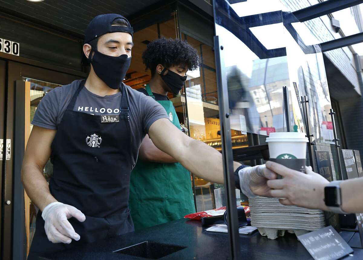 Starbucks shift supervisor Adan Miranda wears a face mask as he serves a drink to a customer while standing behind a plexiglass shield in a booth outside the store in Sacramento, Calif., Thursday, May 21, 2020. Restaurants in Sacramento County are preparing to open for dine in service starting Friday. (AP Photo/Rich Pedroncelli)