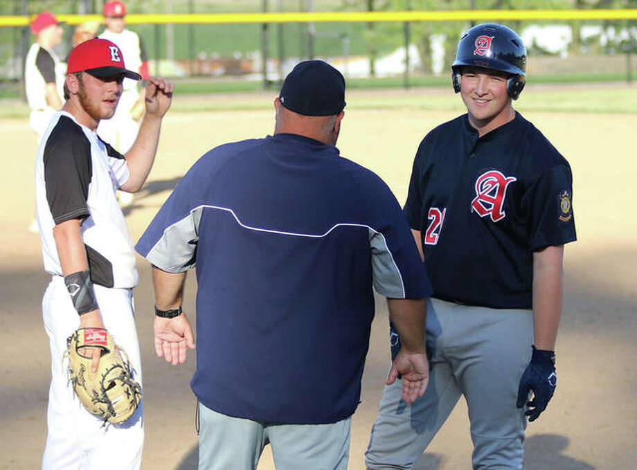 Alton's Gage Booten (right) talks with a teammate in the dugout after his single while first base coach Brian Hanslow chats with Elsberry first baseman Corey Juergensmeyer on Thursday in Elsberry, Missouri. Photo: Greg Shashack | The Telegraph
