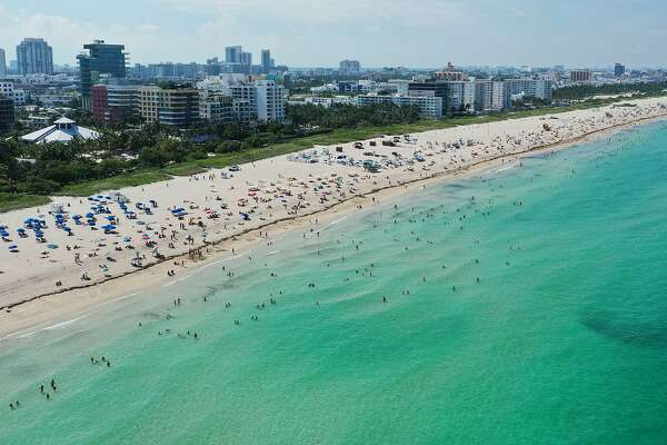 MIAMI BEACH, FLORIDA - JUNE 10: An aerial drone view as beachgoers take advantage of the opening of South Beach on June 10, 2020 in Miami Beach, Florida. Miami-Dade county and the City of Miami opened their beaches today as the area eases restrictions put in place to contain COVID-19. (Photo by Cliff Hawkins/Getty Images)
