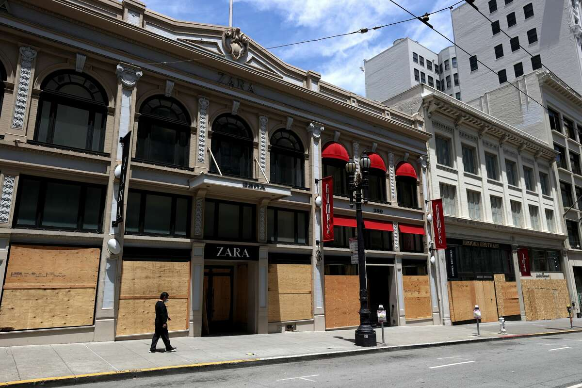 SAN FRANCISCO, CALIFORNIA - JUNE 11: A person walks by a boarded up storefronts on June 11, 2020 in San Francisco, California. Economic worries due to the coronavirus COVID-19 pandemic continue as an additional 1.5 million people filed for first-time unemployment benefits in the past week. The Dow Jones Industrial average plunged over 1,800 points on the news. (Photo by Justin Sullivan/Getty Images)