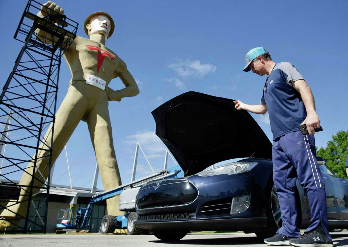 Andrew Nelson lifts the hood of his Tesla Model S in front of the Golden Driller as it gets a Tesla facelift Tuesday, May 19, 2020.Tulsa's iconic Golden Driller statue is joining the effort to help lure automaker Tesla to build its new U.S. assembly plant here. The 75-foot tall statue in the heart of the city is getting a makeover that includes a bright-red Tesla logo on its chest and a mask to make the oil field worker look more like Tesla CEO Elon Musk. City officials plan to unveil the new look at a press conference Wednesday afternoon. (Mike Simons/Tulsa World via AP)