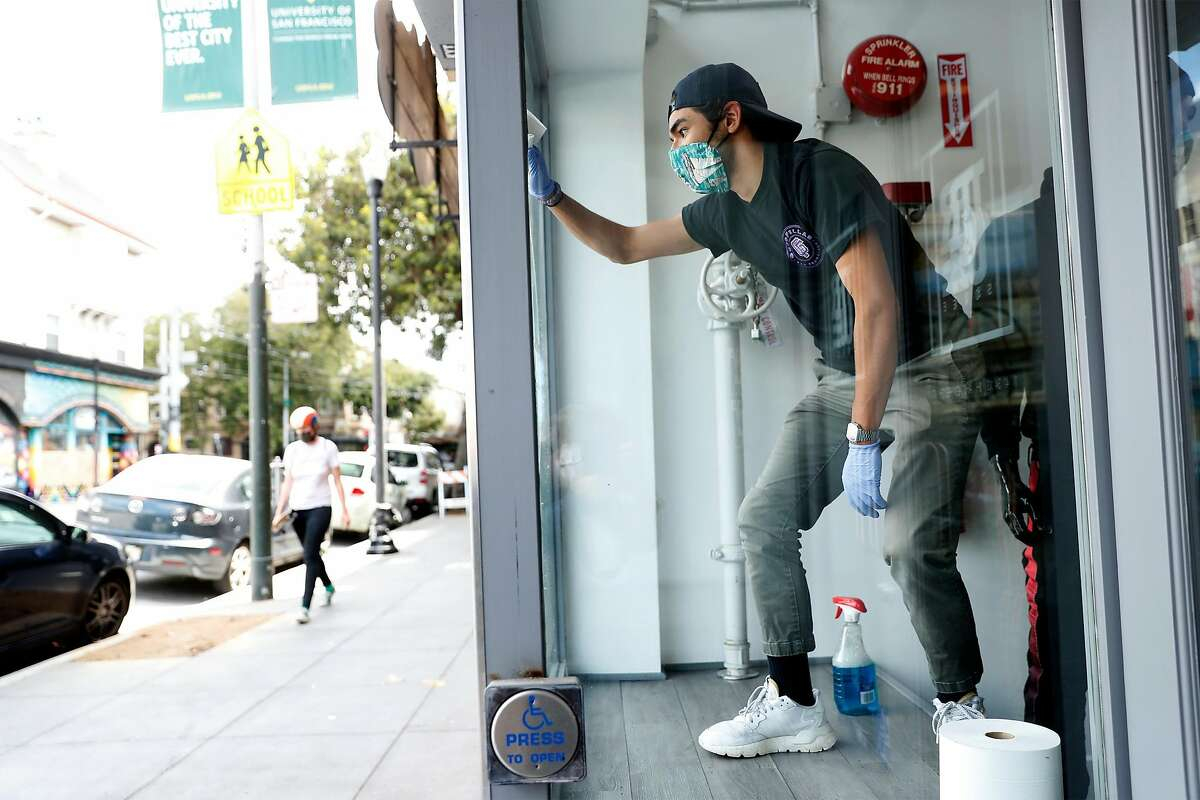 Danny Corleto cleans the windows at True Sole as the shoe store prepares to reopen for curbside pick up on Haight Street in San Francisco, Calif., on Monday, May 18, 2020. Retail stores in San Francisco and other Bay Area counties are now permitted to sell inventory curbside.