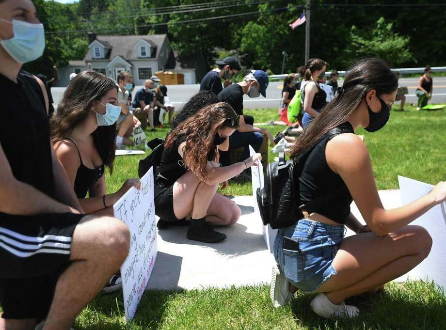 Protestors take a knee for 8 minutes and 46 seconds in recognition of the death of George Floyd during a Black Lives Matter peaceful protest on Route 67 in Oxford on Sunday, June 7. Photo: Brian A. Pounds / Hearst Connecticut Media / Connecticut Post