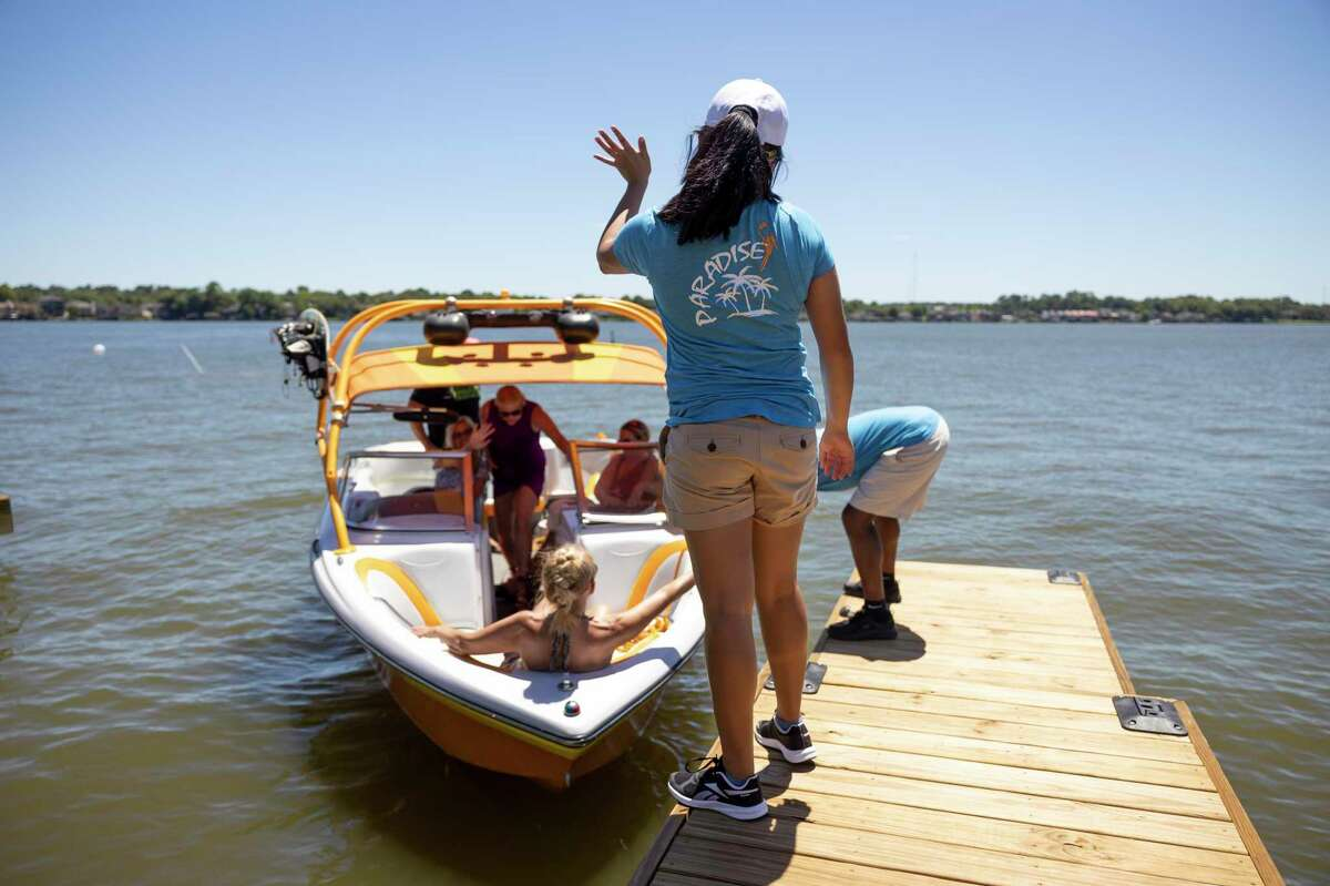 Amy Suarez waves goodbye to visitors at the docking port at LandShark Bar & Grill in Lake Conroe, Thursday, June 11, 2020. The restaurant currently operates at 50 percent capacity.