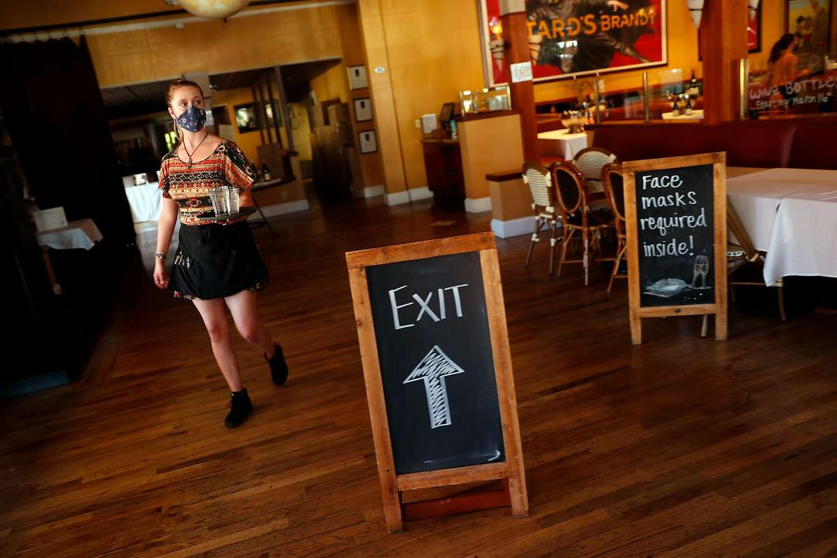 Stephanie Light brings water out to diners at Left Bank Brasserie in Larkspur, Calif., on Wednesday, June 10, 2020. The French restaurant is open for outdoor dining only.