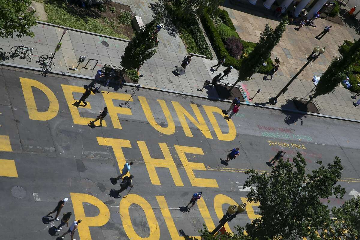"""WASHINGTON, DC - JUNE 08: People walk down 16th street after Defund The Police was painted on the street near the White House on June 08, 2020 in Washington, DC. After days of protests in DC over the death of George Floyd, DC Mayor Muriel Bowser has renamed that section of 16th street """"Black Lives Matter Plaza"""". (Photo by Tasos Katopodis/Getty Images)"""