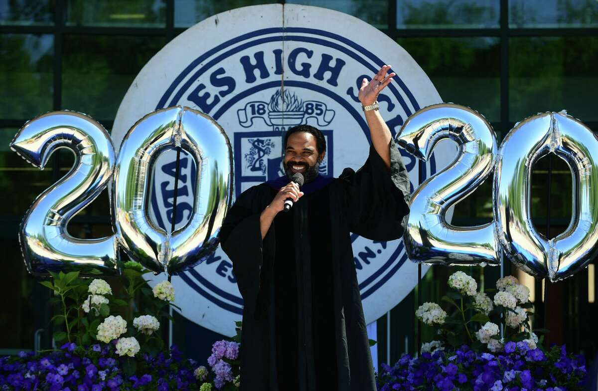 Principal Stafford Thomas Jr welcomes the Class of 2020 graduates as they ride in a motorcade to Staples High School for a drive-through commencement ceremony Friday, June 12, 2020, in Westport, Conn.