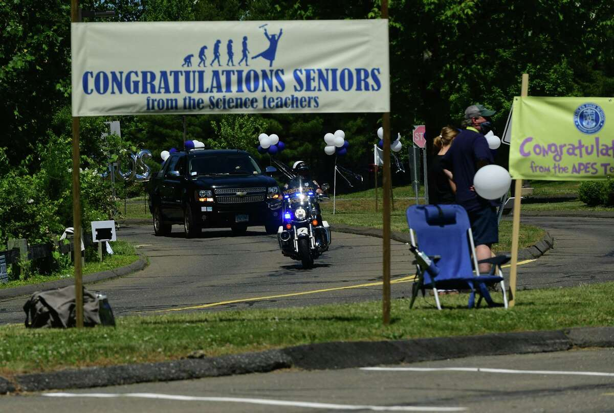 Class of 2020 graduates join in a motorcade to Staples High School for a drive-through commencement ceremony Friday, June 12, 2020, in Westport, Conn.