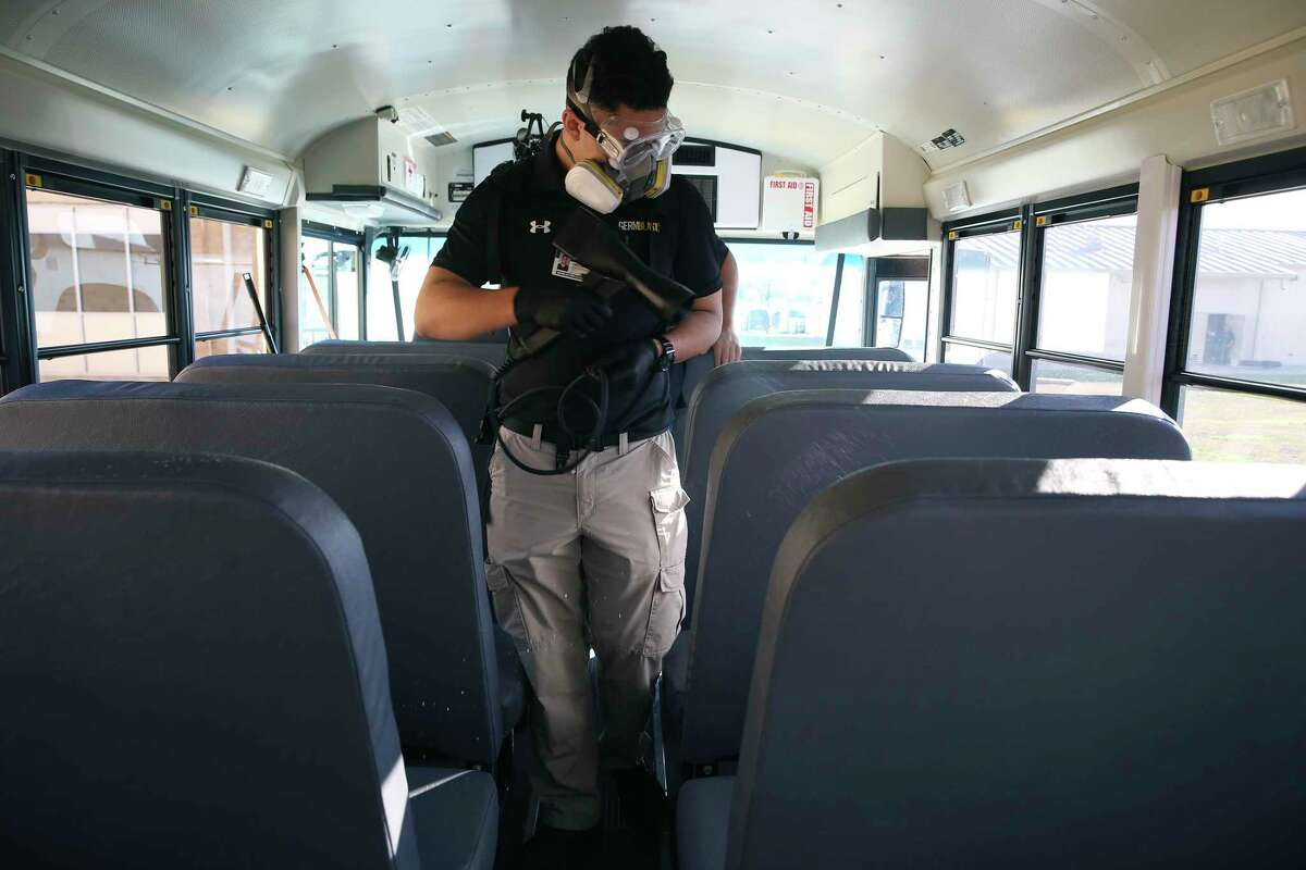 Christopher Sierra, with Germblast, sprays an electrostatic charged film of disinfectant inside a school bus at East Central High School, Wednesday, March 4, 2020. The company was demonstrating how it disinfects various surfaces on school buses, classrooms and locker rooms.