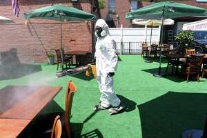 Bradford McIlvaine of Sole Source Restoration sprays a virucide at the outdoor seating area for Adriana's Restaurant and Wine Bar in New Haven to kill the pathogens associated with COVID-19 during a demonstration on June 12, 2020.