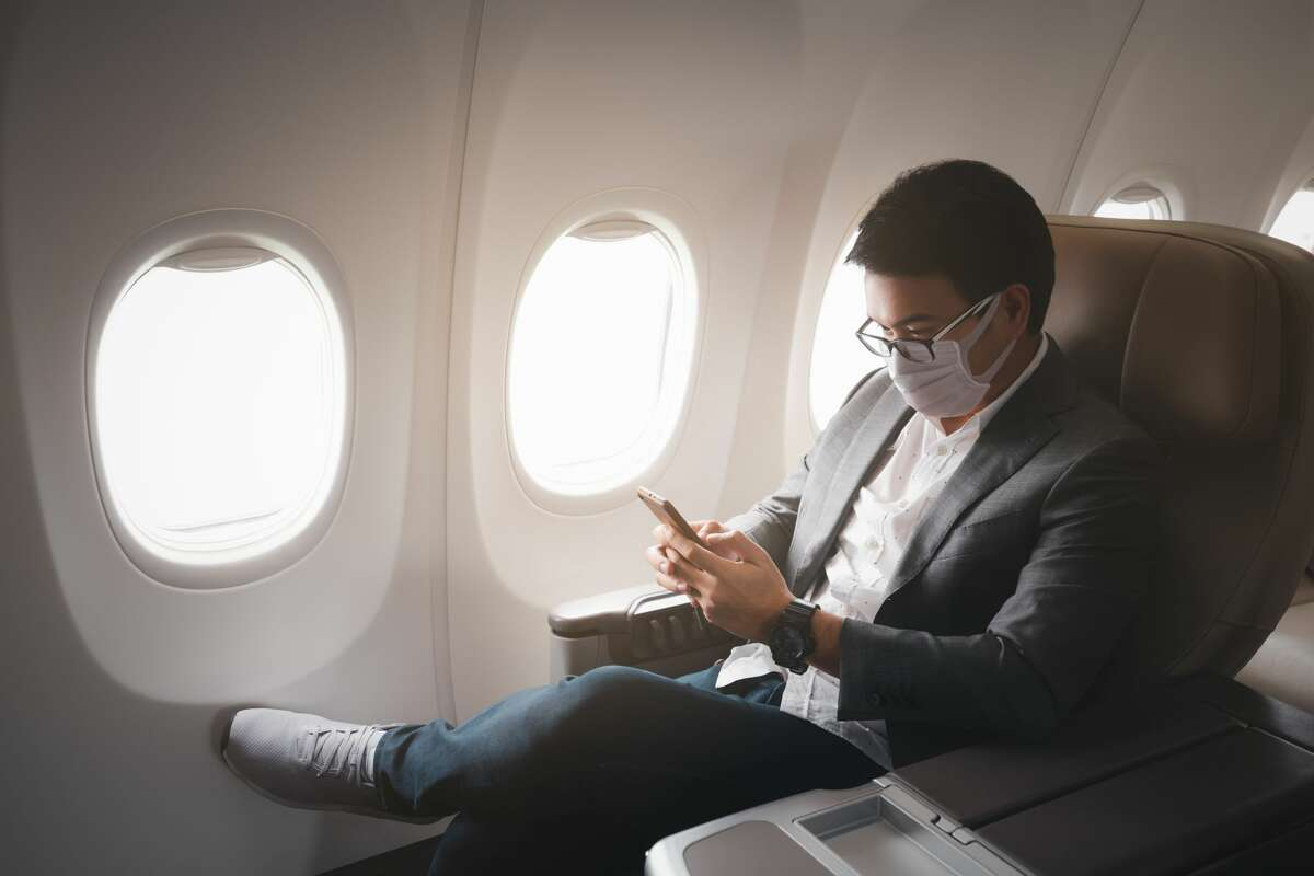 Young businessman wearing protective face mask in business first class amid COVID-19 pandemic.