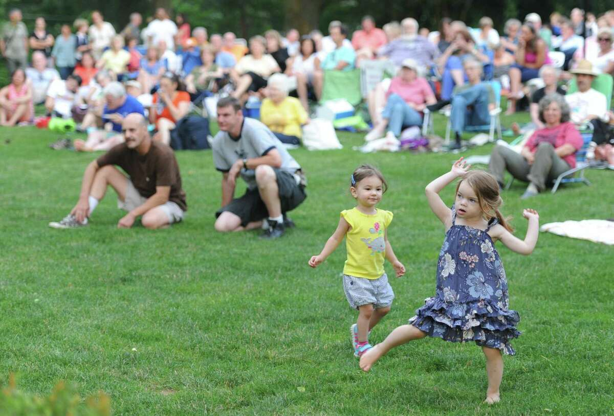 Audrey Endee, right, 3, and Reese Pettitt, 2, of Ridgefield, dance to the mountain music of 3 Penny Acre during the CHIRP free concert at Ballard Park.