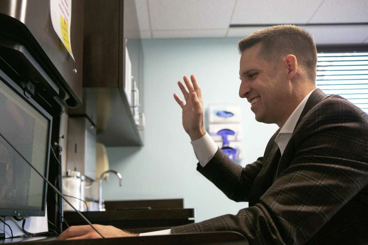 Dr. Matthew Harting greets his patient during a telemedicine appointment in his office at UT Physicians on June 08, 2020.