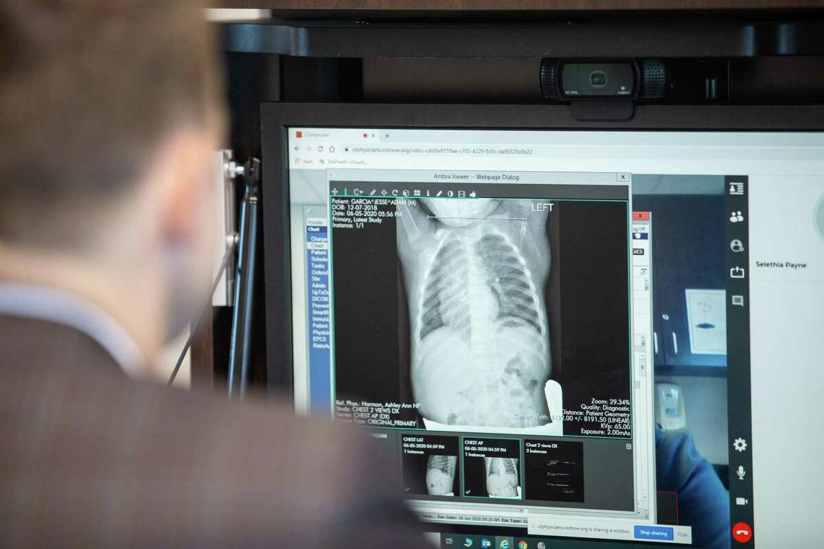 Pediatric surgeon Matthew Harting shares a chest x-ray with his patient's mother while on a telemedicine video call at UT Physicians on June 08, 2020.
