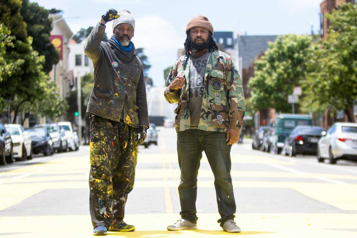 (Left to right) Artists Malik Seneferu and Derrick Rtystk Shavers helped plan and paint the Black Lives Matter mural. Each word is painted in bright yellow letters and spans almost the entire street.