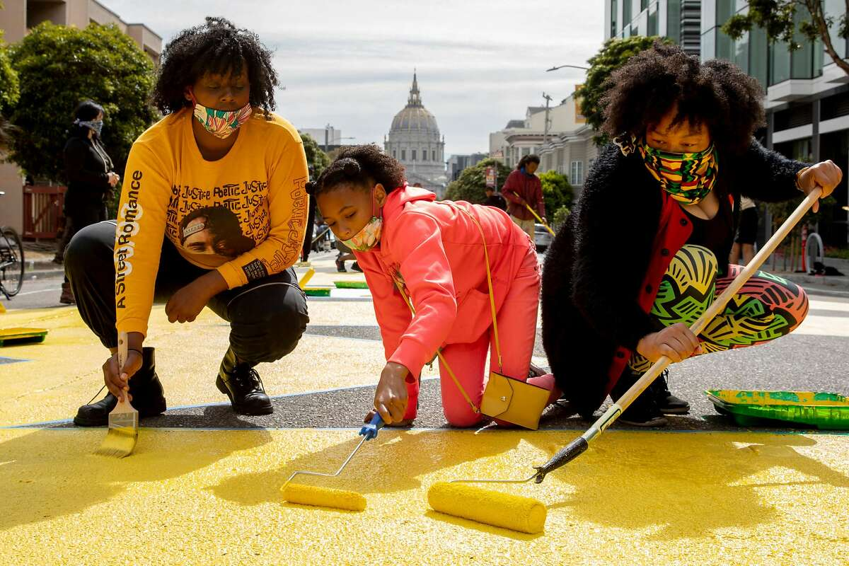 """(From left) Ashley Williams, her 10-year-old daughter Marley McNealy and Williams' sister Mo McNealy work alongside volunteers and staff African American Art & Culture Complex work to paint massive letters spelling """"Black Lives Matter"""" across Fulton Street between Webster and Octavia streets in San Francisco, Calif. Friday, June 12, 2020. �I thought it was important as an SF native to show support for community because there aren�t that many Black natives left� says Mo. �For me, it�s paying homage to that because that was done purposefully. I�m honoring my childhood friends. People don�t understand when you aren�t from here you get to go back to your hometown and the people you grew up with are still there. But for me, it�s not the same and it�s hurtful to know that this government has done Black residents so bad. And I will continue to fight for our black residents because I miss my community.�"""