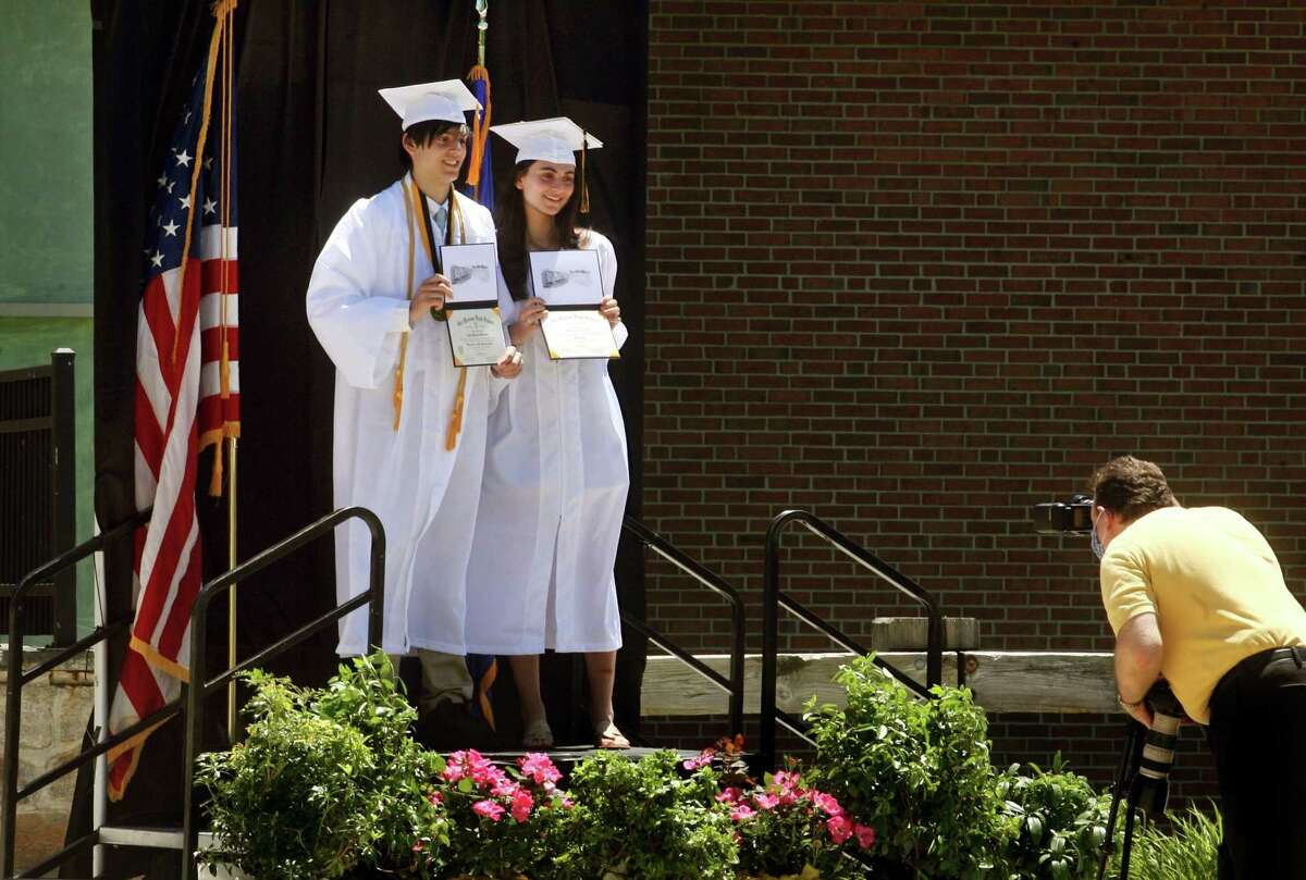Twins Luke and Hannah Weregles pose together for photos with their diplomas during Joel Barlow High School's Commencement in Redding, Conn., on Friday June 12, 2020. Social distancing played a big part in the ceremony. Student were dropped off so they could each walk up to get their diploma off a table. After a quick official photo, students then go back in the family vehicle a drove past teachers lined up along the road.