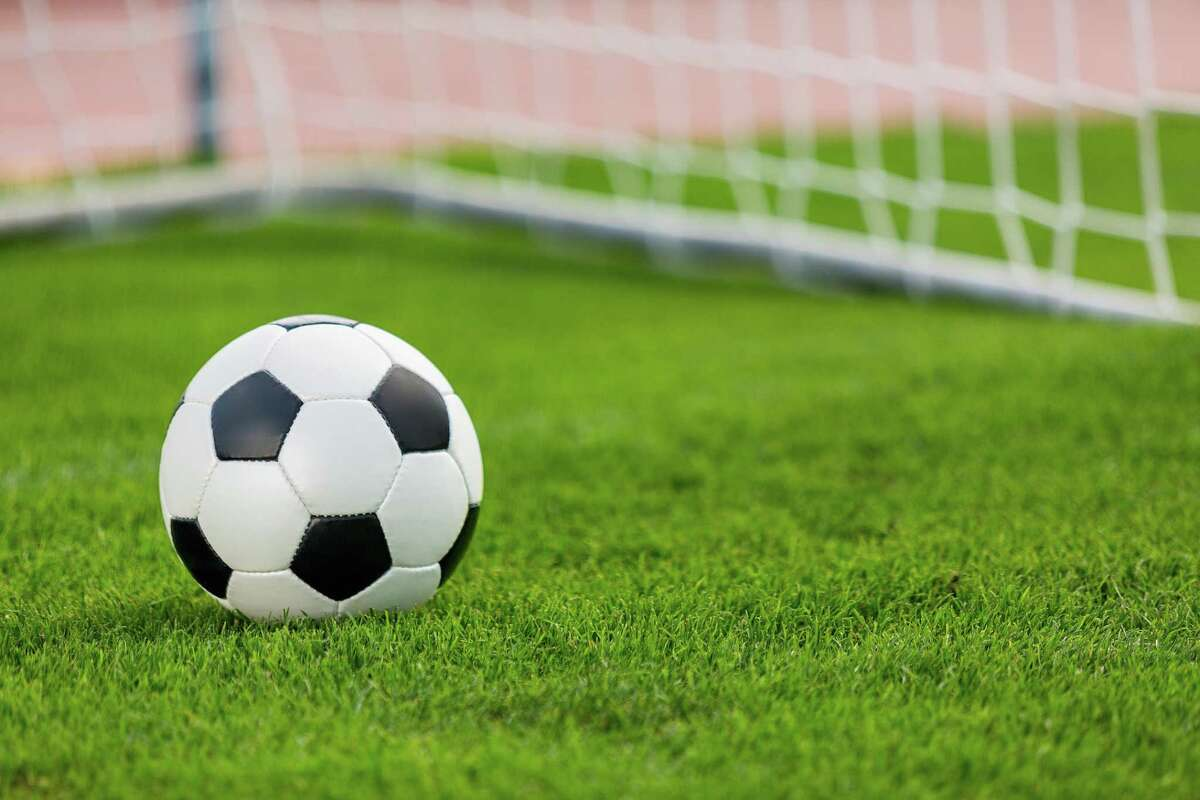 Closeup of a soccer ball and goal post.