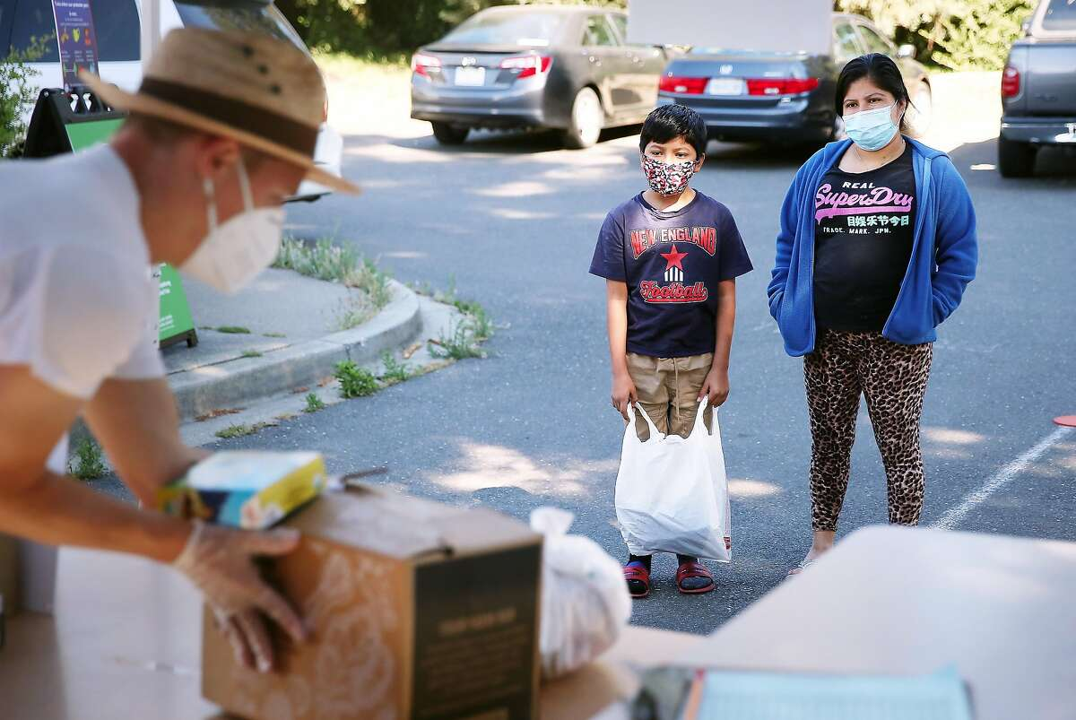 Florentina Sen (right) stands next to her son Wilmer Martinez (center), 11, both of Oakland, as volunteer Kent Kessinger (left) stacks bags and boxes on a table as Sen and Martinez wait in ine to pick up meals at a school meal distribution site at Esperanza Elementary School on Monday, June 8, 2020 in Oakland, Calif.