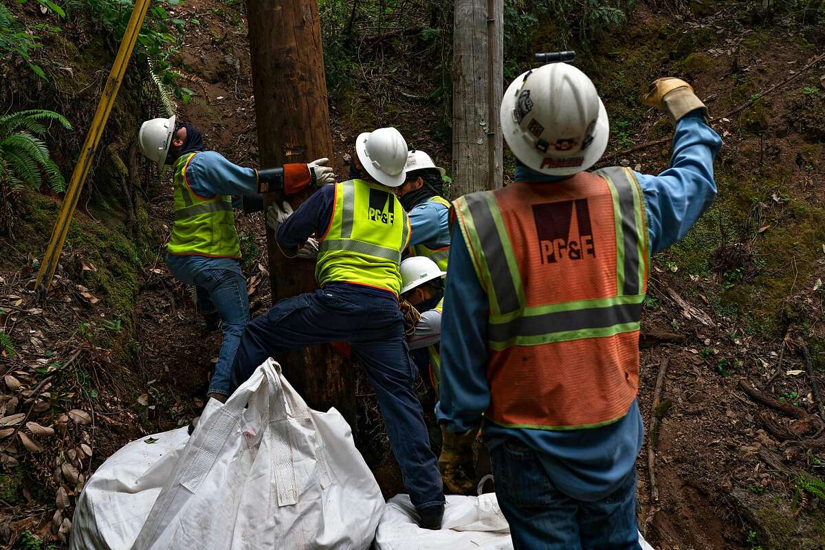 A PG&E crew replaces older wood power poles at Odd Fellows Park with more resilient ones that are less likely to become broken during windstorms and cause wildfires. Guerneville, California on June 12, 2020.