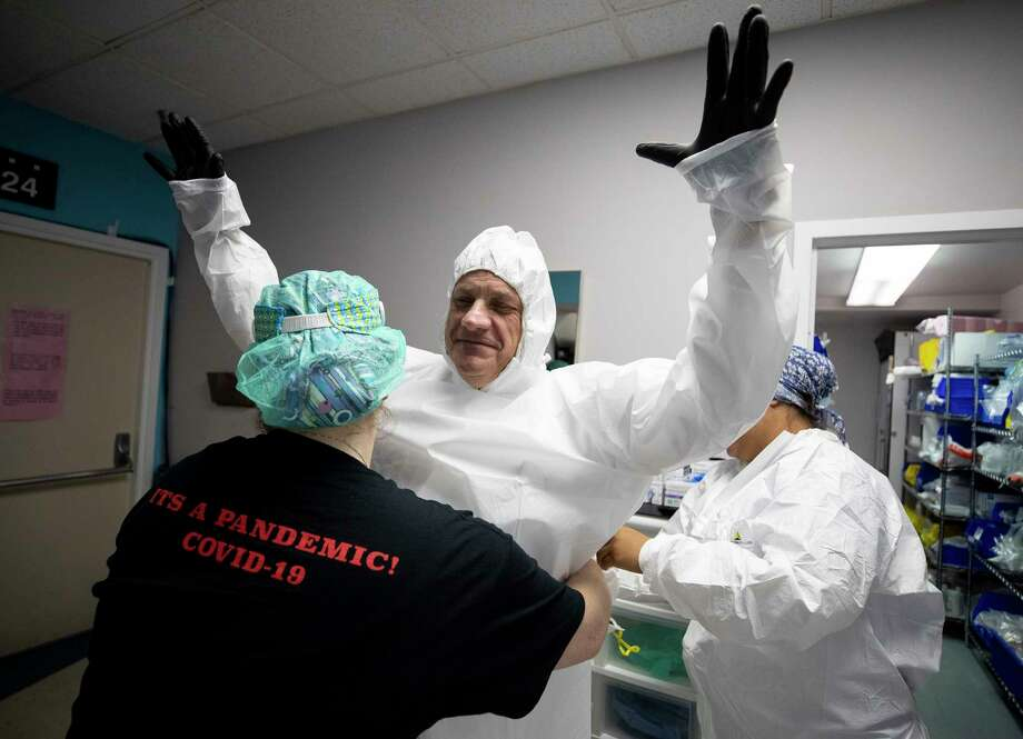 Dr. Joseph Varon, center, and his medical staff get into PPE before heading going inside the COVID-19 intensive care unit at United Memorial Medical Center on Thursday, June 11, 2020, in Houston. The state of Texas has seen a spike in COVID-19 cases. Photo: Godofredo A. Vásquez, Staff Photographer / © 2020 Houston Chronicle