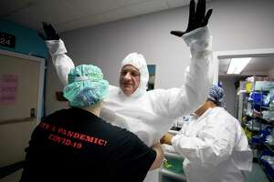 Dr. Joseph Varon, center, and his medical staff get into PPE before heading going inside the COVID-19 intensive care unit at United Memorial Medical Center on Thursday, June 11, 2020, in Houston. The state of Texas has seen a spike in COVID-19 cases.